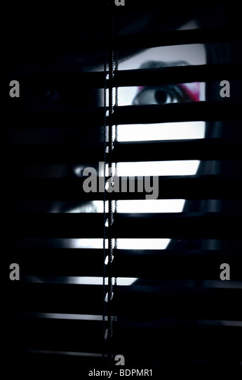 A partially hidden face of a young woman behind a screen - Stock Image