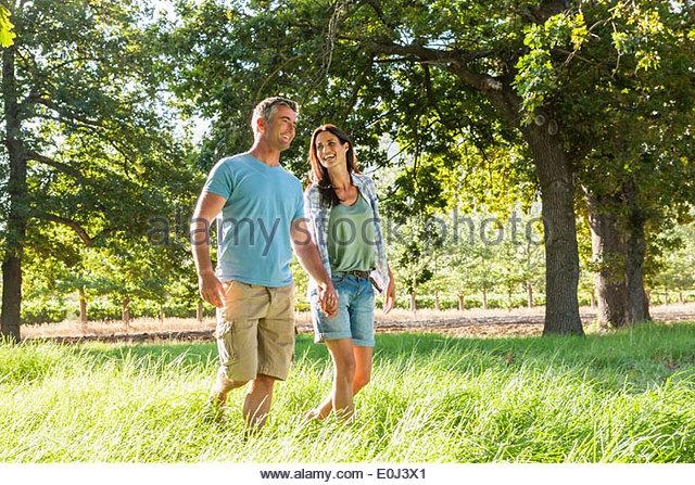 Romantic Couple Enjoying Walk In Beautiful Countryside - Stock Image