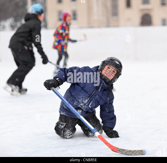 Young boys playing ice hockey on an outdoor rink, Winnipeg, Manitoba, Canada - Stock Image