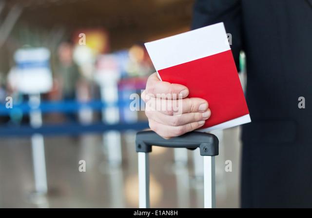 close up of passport and ticket in hand in airport - Stock-Bilder