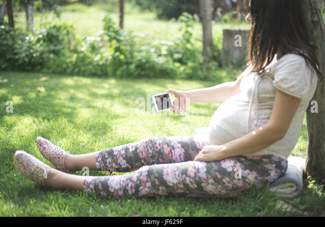 Pregnant women with smartphone. - Stock Image