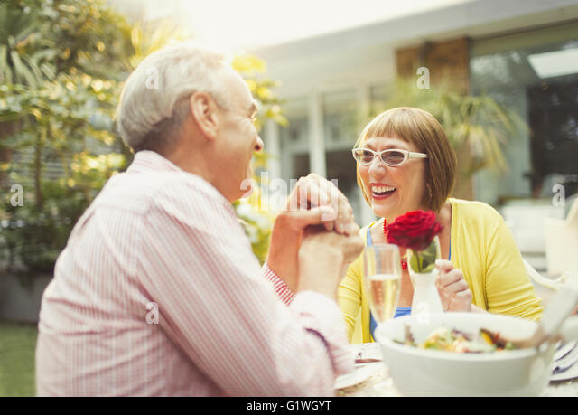 Smiling mature couple enjoying lunch in garden - Stock Image