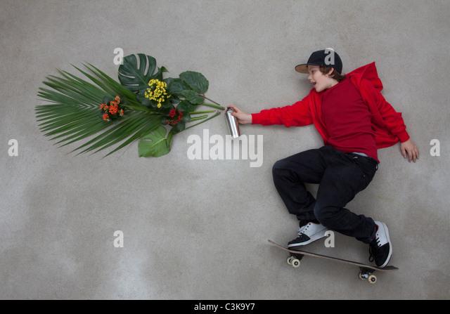 Boy spraying leaves from spray bottle - Stock Image