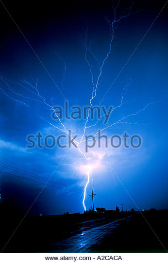 Lightning Bolt with road highway and power pole showing a positive  strike. - Stock Image
