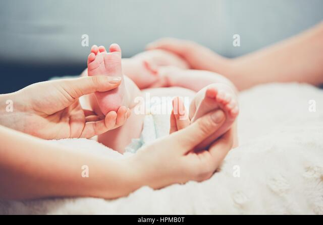 Touch of the parent love. Couple caress their little baby in the bed. - Stock Image