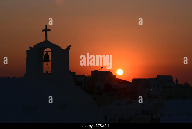 Silhouette of a Greek church during the world-famous sunset seen from Oia , in Santorini island, Greece. - Stock Image