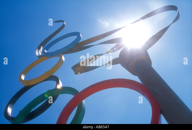 A sculpture of the Olympic Torch, the flame seemingly lit by the sun, with Olympic rings symbol, in Alimos, Athens, - Stock Image