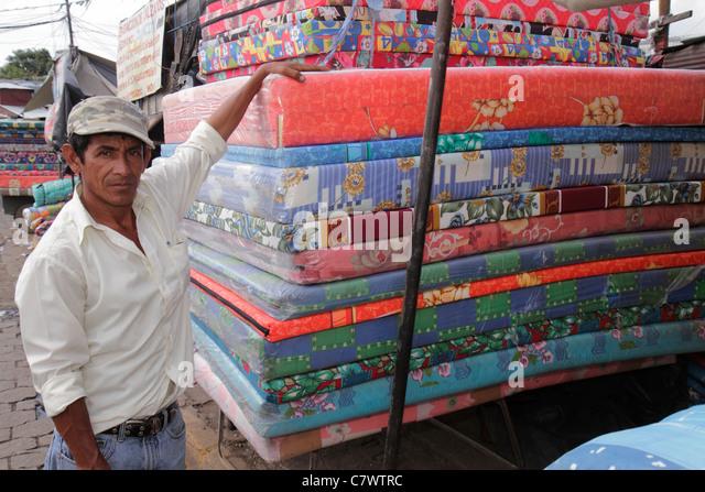 Managua Nicaragua Mercado Oriental flea market marketplace shopping vendor merchant Hispanic man job inexpensive - Stock Image