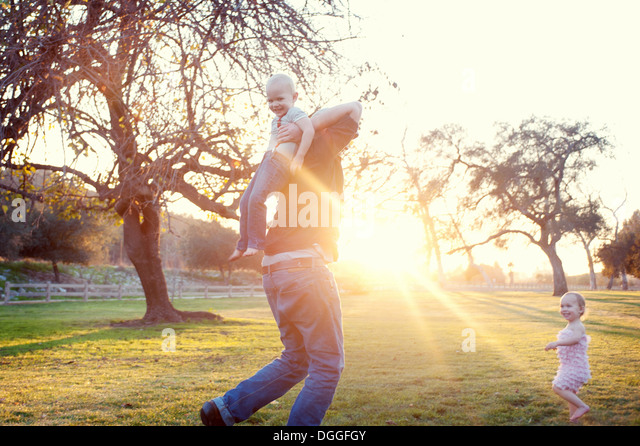 Father carrying son in sunlit field - Stock-Bilder