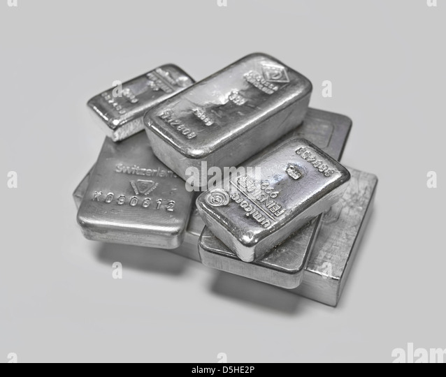 Silver bullion bars in a pile on plain background - Stock Image