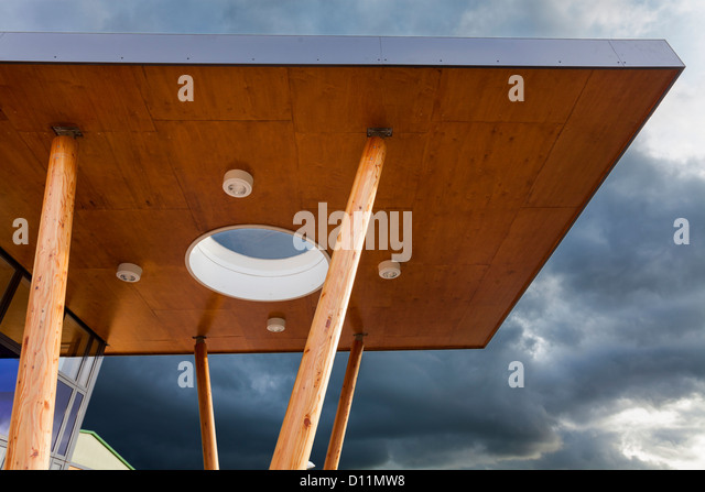 Modern architecture canopy with wooden pillars against sky. - Stock Image