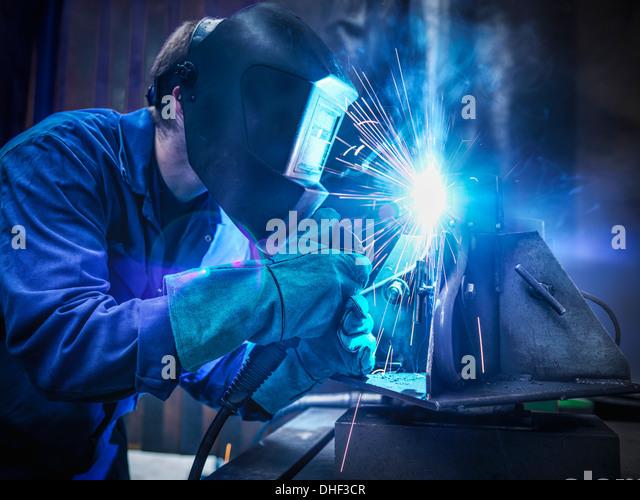 Welder wearing face mask and protective gloves in factory - Stock Image