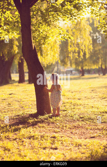 alone toddler playing near the tree - Stock Image