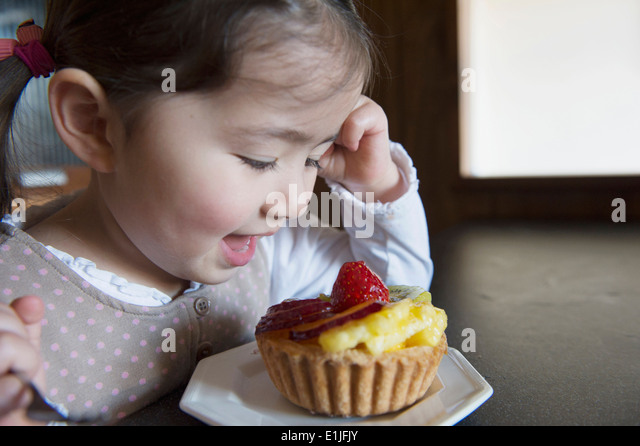 Girl happy with her tart - Stock Image