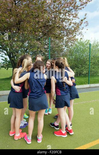 Group of girls in huddle on sports field - Stock Image