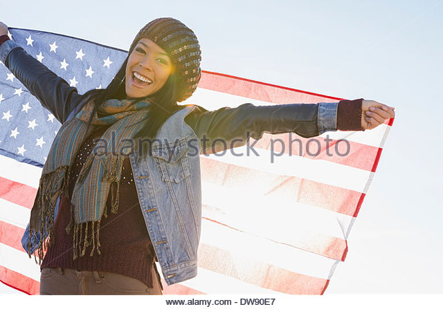 Portrait of smiling woman holding American flag against clear sky - Stock Image