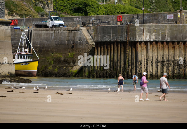 People walking on Towan Beach, Newquay with the harbour in the background. - Stock Image