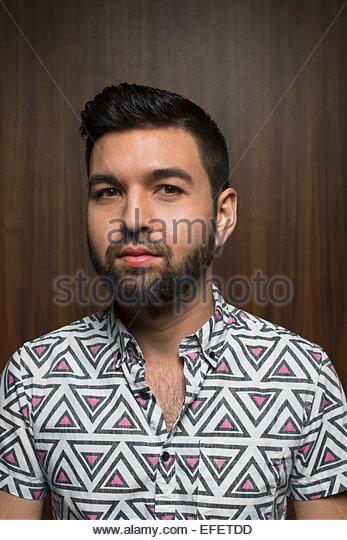 Portrait of bearded man in geometric patterned shirt - Stock Image