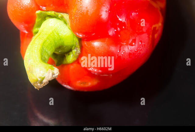 Red pepper on black background - Stock Image