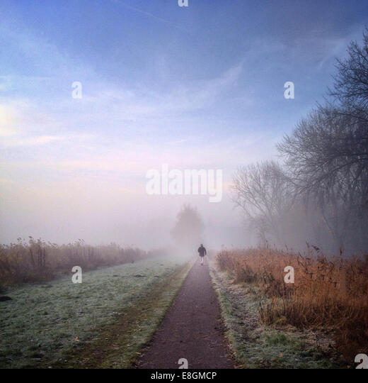 Man walking down path on misty morning - Stock Image