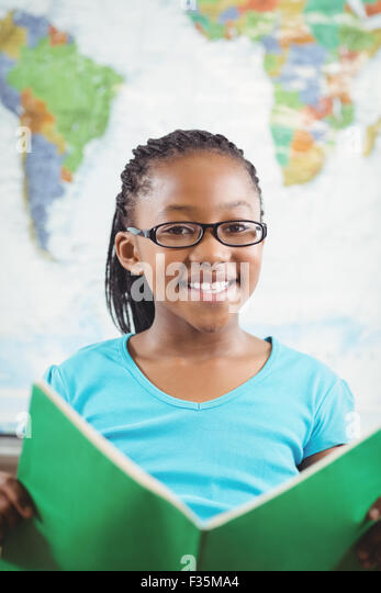 Smiling pupil reading book in a classroom - Stock Image