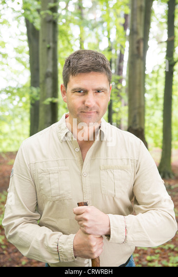 Mid adult man standing in a forest holding a walking stick and  looking at the camera - Stock Image