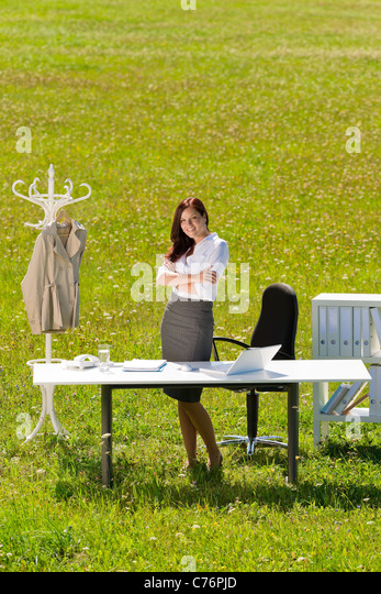 Young businesswoman in sunny meadow office smiling standing behind table - Stock Image