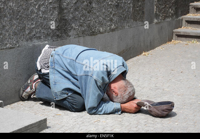 One of the many people begging on the streets of Prague, lying on their knees, holding a cap in front of them, hiding - Stock Image
