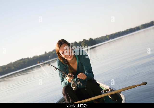 Woman fishing from canoe - Stock Image