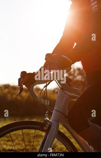 Cyclist riding during sunset - Stock Image