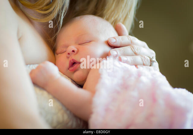 Gentle Hands of Mother Holding Her Precious Newborn Baby Girl. - Stock Image