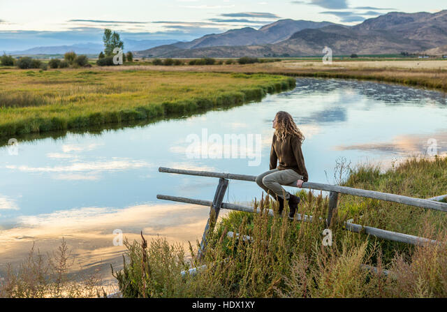 Caucasian woman sitting on wooden fence near mountain river - Stock Image