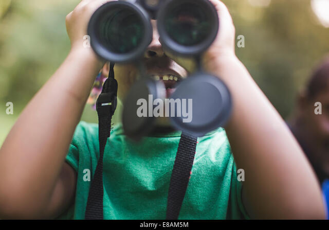 Close up of girl looking through binoculars in forest eco camp - Stock-Bilder