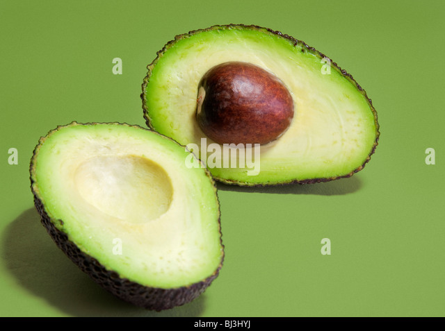 Hass variety avocado pear sliced into two halves against a green background. - Stock Image