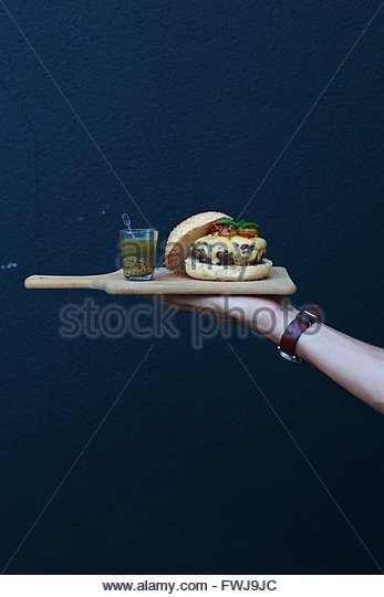 Cropped Hand Holding Burger And Drink On Cutting Board Against Wall - Stock-Bilder