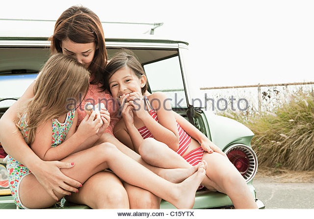 Mother and daughters eating sandwiches on car boot - Stock-Bilder