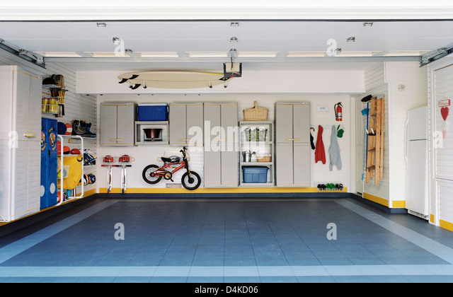 Surfboards and bicycles in empty garage - Stock Image