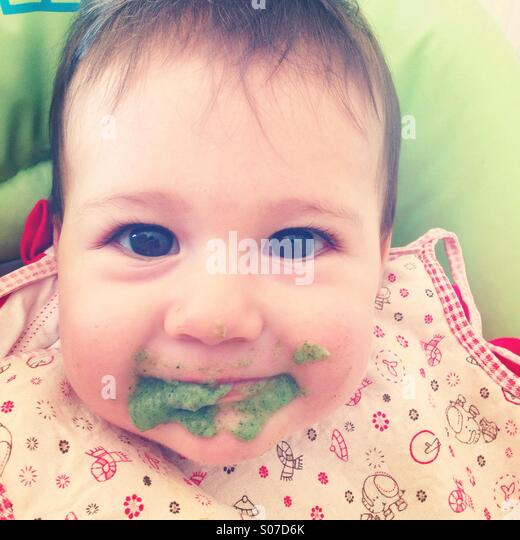 Baby with mouth full of spinach - Stock-Bilder