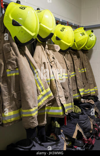 Firefighters protective clothing and helmets neatly arranged for quick response - Stock Image
