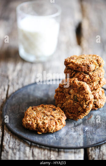 traditional anzac oat cookies and glass of milk on a wooden background - Stock Image