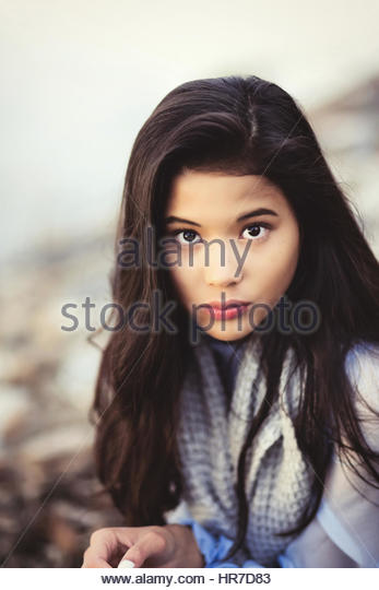 Dark haired young woman by the water - Stock Image