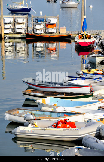 Rockland Harbor Maine with colorful boats skiffs dinghies sailboats moored to pier dock quay vertical - Stock Image