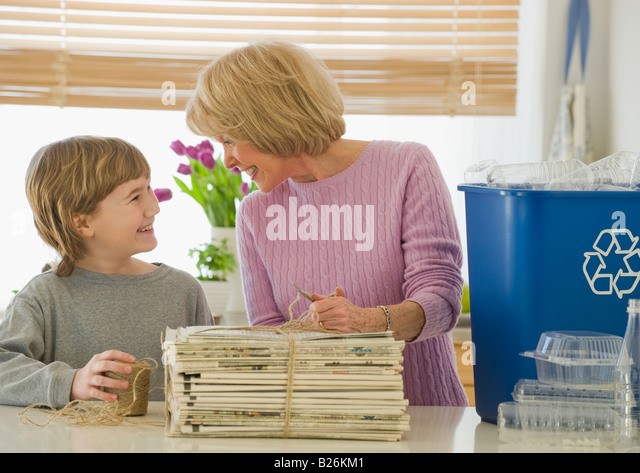 Grandmother and grandson recycling newspapers - Stock Image