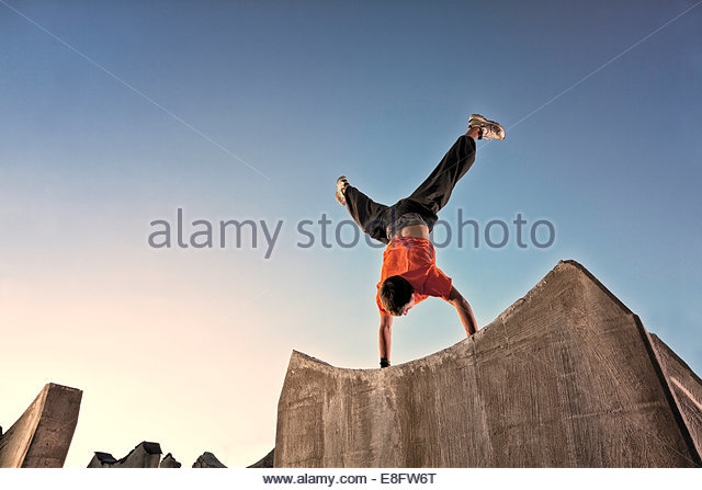 Man doing parkour handstand on edge of wall, Colorado, America, USA - Stock Image