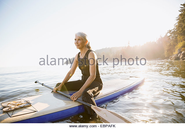 Senior woman on paddle board in ocean - Stock Image