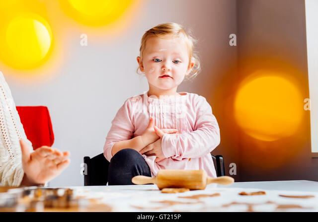 Girl looking at pastry dough while standing besides mother - Stock-Bilder