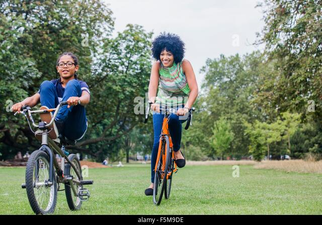Front view of mother and son riding on bicycles smiling - Stock Image