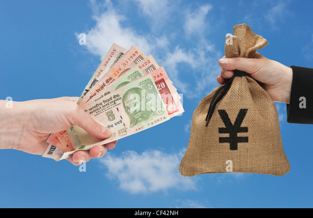 Many diverse Indian rupee bills are held in the hand. At the other side a money bag with Japanese Yen currency sign. - Stock-Bilder