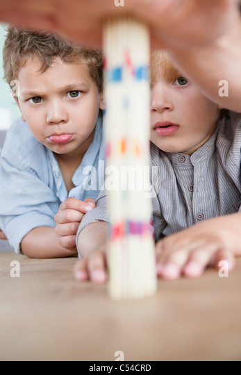 Boys looking at pick up sticks - Stock Image