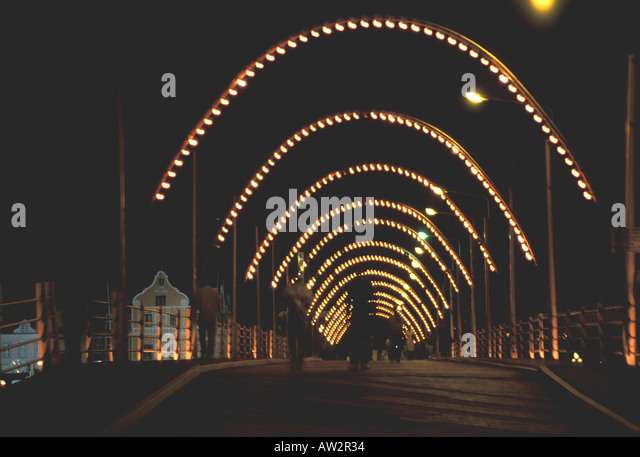 queen emma bridge at night crossing the shipping channel at willemstad curacao - Stock Image